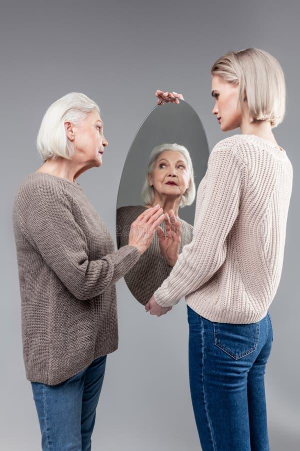 接触卵形镜子的表面好奇老妇人在她的女儿的手上 库存照片