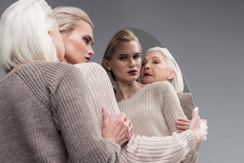 接触她的女儿手的可怕灰发的老母亲 免版税图库摄影