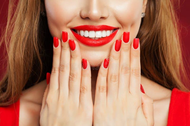 接触她的面孔的完善的妇女她的有修指甲的手 有红色口红和红色指甲油的,发廊概念构成嘴唇 库存照片