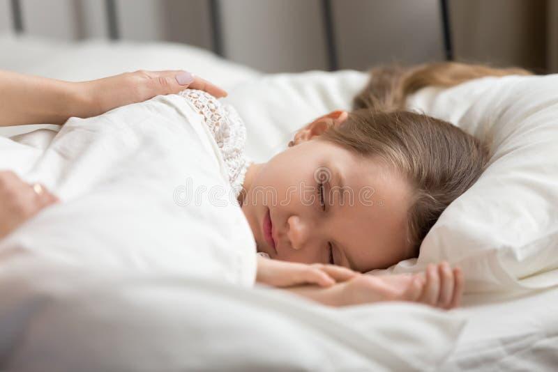 接触睡觉的孩子女儿的妈妈手叫醒小孩 免版税库存照片
