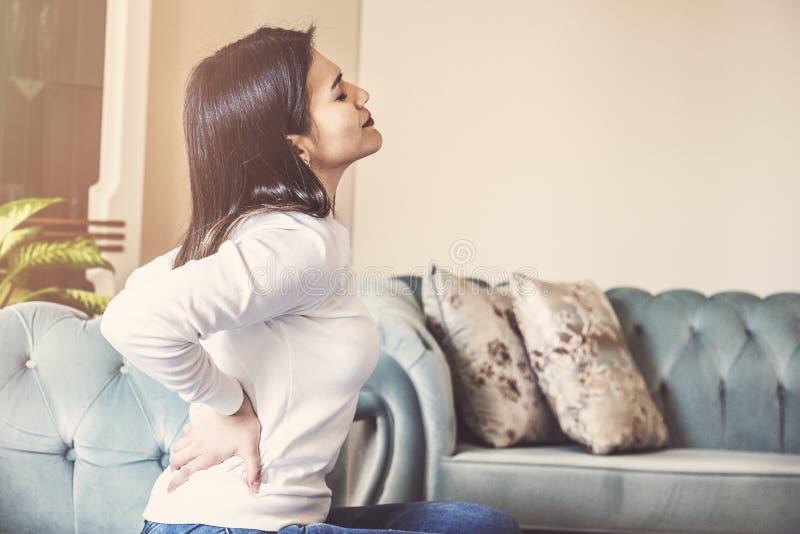 接触背部疼痛的女性手坐在家休息的沙发 年轻女人低腰部创伤按摩 图库摄影