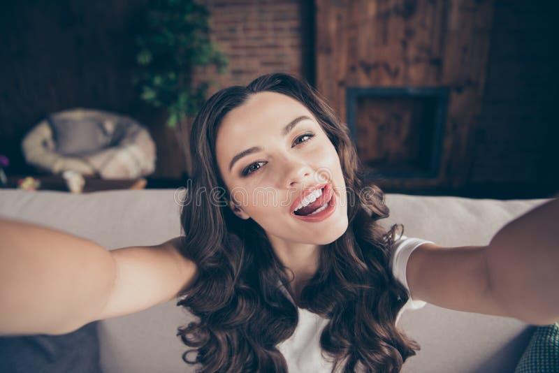 接近的照片美丽的浅黑肤色的男人她她的夫人笑笑声做采取selfies舔上嘴唇的轻的调情的人舌头 免版税库存图片
