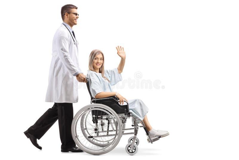 推挤轮椅挥动的年轻男性医生一名女性患者 库存图片
