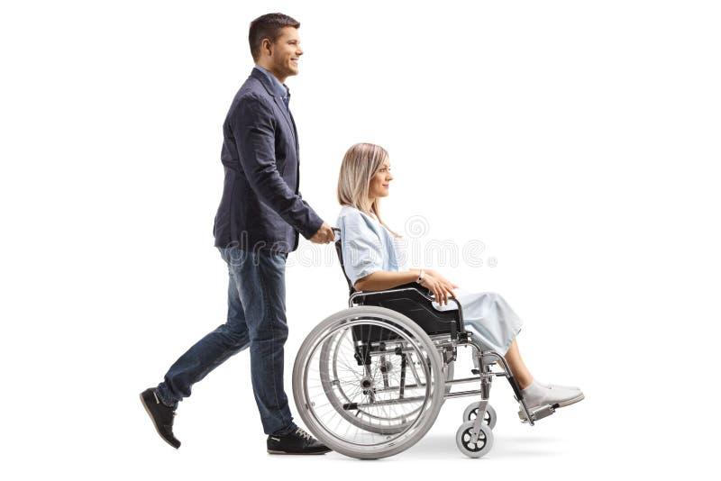 推挤轮椅的年轻人一年轻女人 免版税库存图片