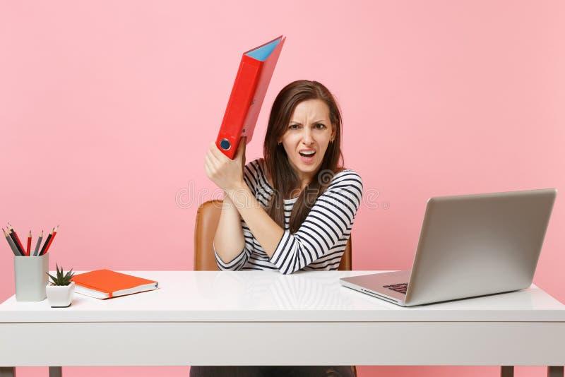 掩藏在与研究项目一会儿的纸张文件的红色文件夹后的被激怒的妇女在有被隔绝的膝上型计算机的办公室坐 免版税库存照片