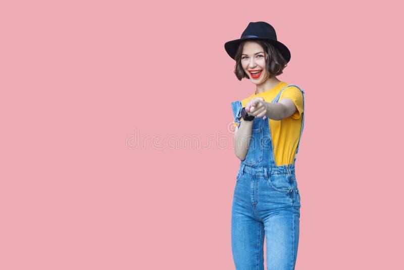惊奇的美丽的年轻女人画象黄色T恤杉、蓝色牛仔布总体有构成的和黑帽会议身分的,惊奇, 库存图片