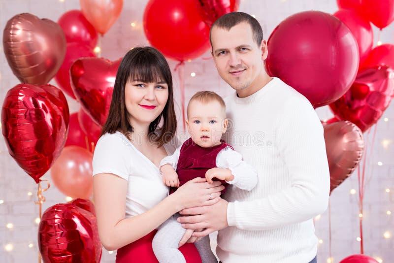 情人节概念-与逗人喜爱的女儿的年轻家庭在红色心形的气球背景 库存图片