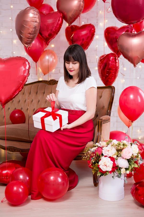 情人节概念-年轻女人全长画象坐葡萄酒沙发和打开的礼物盒有红色心形的 库存照片