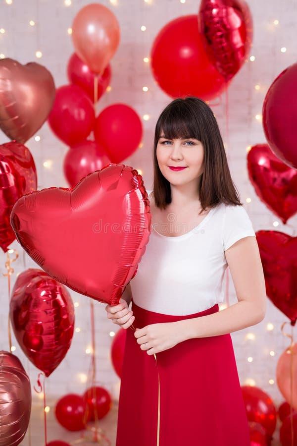 情人节概念-年轻美女画象有红色心形的气球的 库存图片