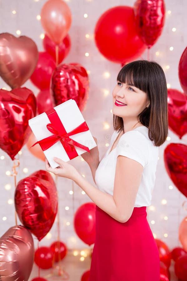 情人节概念-在红色气球背景的愉快的作的妇女藏品礼物盒 库存照片
