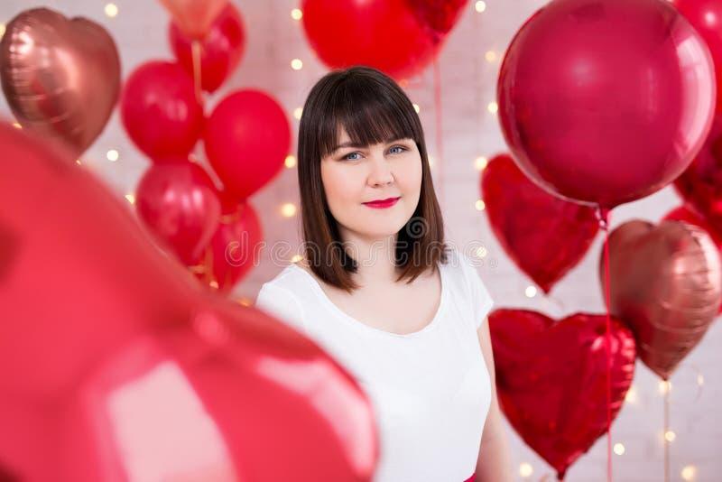 情人节概念-有红色心形的气球的美女 免版税库存图片