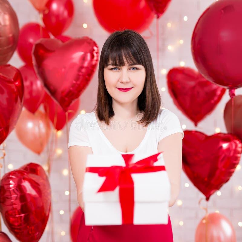 情人节概念-愉快的美女画象有礼物盒和红色气球的 图库摄影