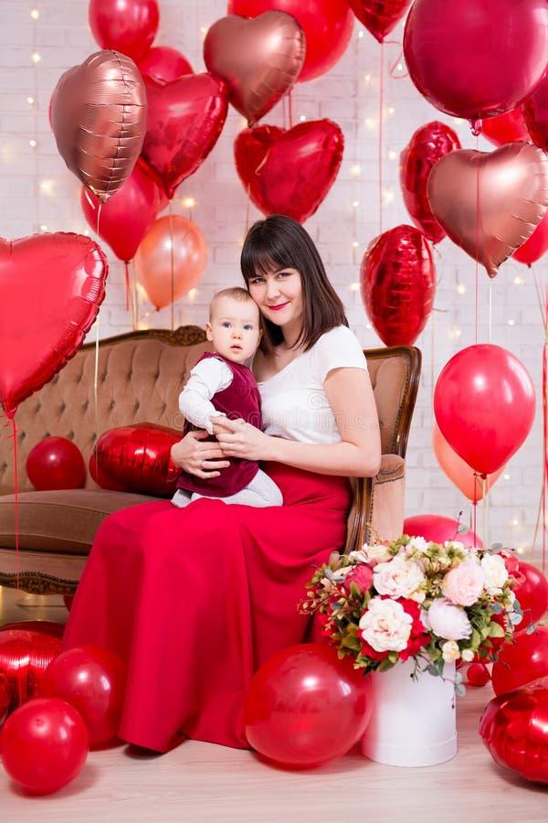 情人节概念-拿着有礼物盒和红色心形的气球的年轻女人一点女儿 免版税库存照片