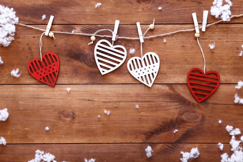 情人节爱背景,垂悬在与落的雪,愉快浪漫的棕色木桌上的红色白色装饰心脏 免版税库存图片