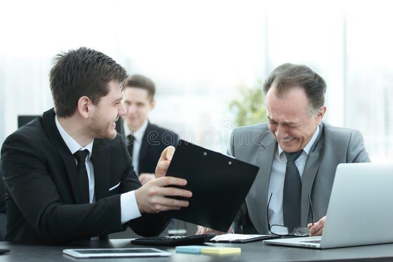 成人商人谈话与一个年轻同事在办公室 库存图片