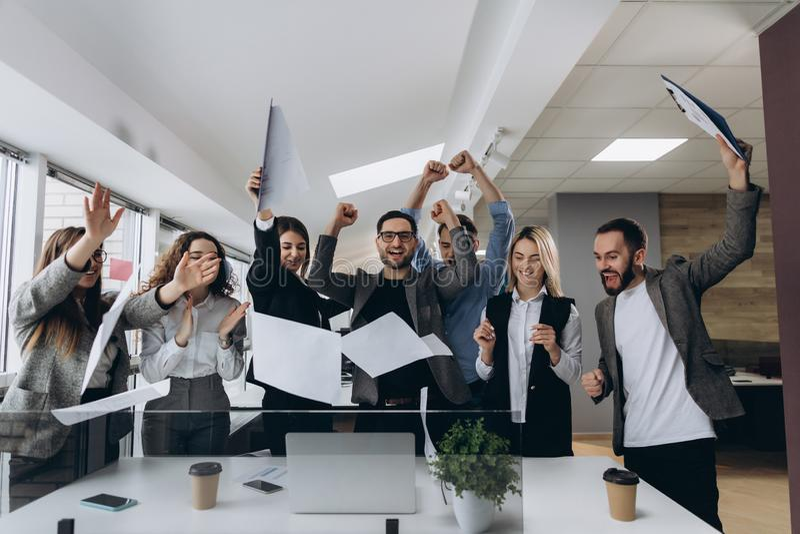 成功和赢取的概念-庆祝胜利的愉快的企业队在办公室 免版税库存图片