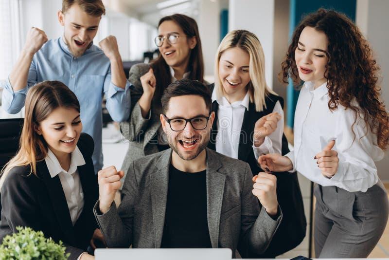 成功的年轻商人举在拳头的手并且尖叫充满幸福,当与在事务时的一台计算机一起使用 免版税库存图片