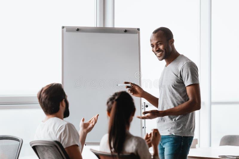 成功的商人支持的whiteboard和解释数据对同事在介绍时 免版税库存照片