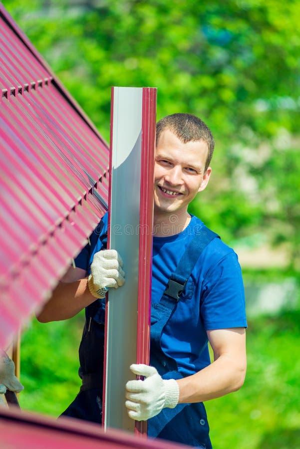 成功的老练的安装工在一个私有房子的屋顶的背景中 库存照片