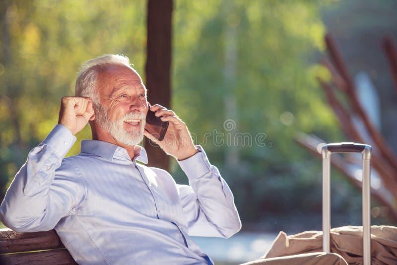 成熟人画象谈话在被弄脏的背景的手机 免版税库存图片