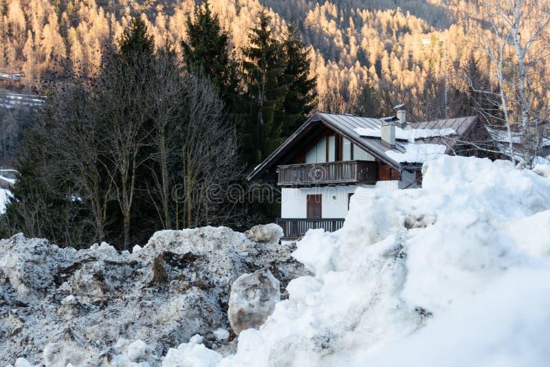 房子的看法在巨大的随风飘飞的雪后的反对山的背景在欧洲 免版税库存照片