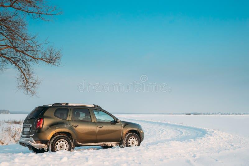 戈梅利,白俄罗斯 汽车雷诺喷粉器或达基亚喷粉器Suv在冬天斯诺伊领域乡下风景停放了 喷粉器 库存图片