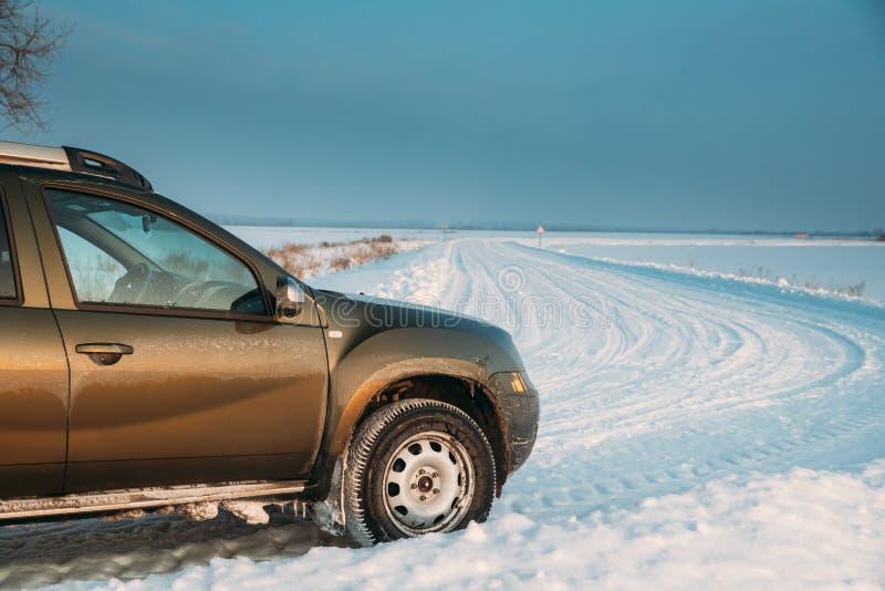 戈梅利,白俄罗斯 汽车雷诺喷粉器或达基亚喷粉器Suv在冬天斯诺伊领域乡下风景停放了 喷粉器 免版税库存照片