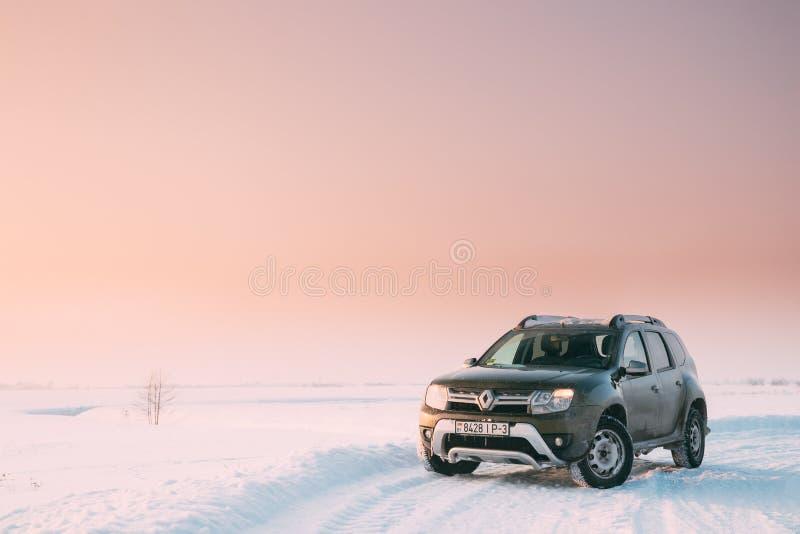 戈梅利,白俄罗斯 汽车雷诺喷粉器或达基亚喷粉器Suv在冬天斯诺伊领域停放了在日落黎明日出 库存图片