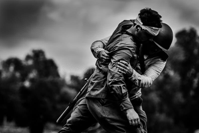战士帮助给他受伤的朋友 库存图片