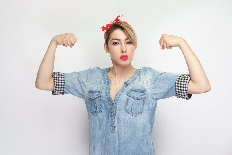 我坚强 独立骄傲的满意的美丽的年轻女人画象蓝色牛仔布衬衣的,构成,红色头饰带身分, 免版税库存照片