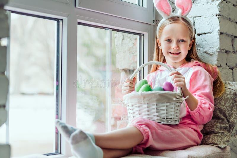 我有复活节心情 兔子服装的美丽的女孩在家坐窗台并且拿着篮子  免版税库存图片