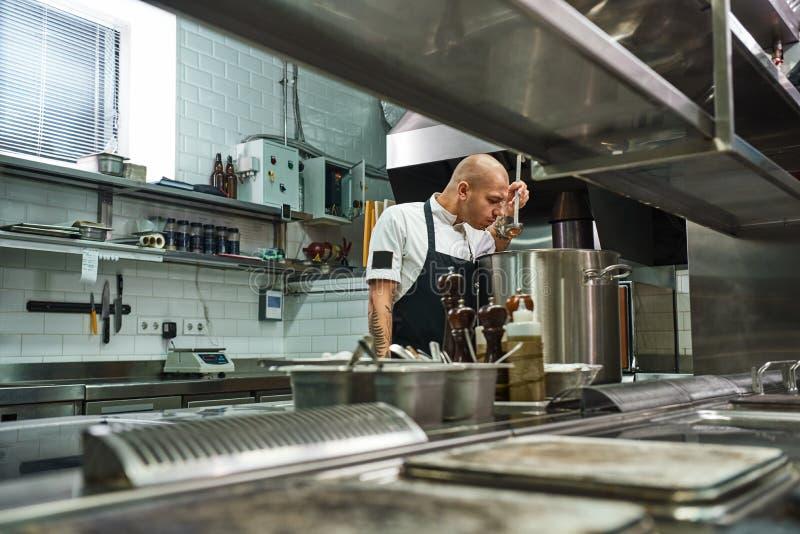 我的著名汤 厨师侧视图围裙的与在他的嗅到汤的胳膊的纹身花刺在餐馆厨房里 库存图片