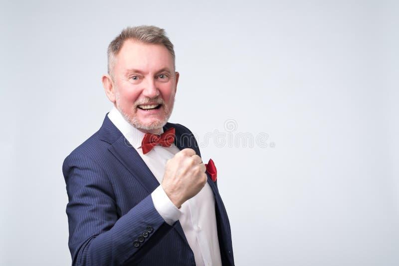 我现在赢得了 微笑愉快的老人打手势和 免版税库存图片