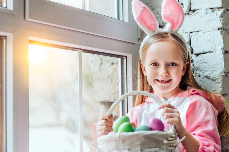 我爱复活节!兔子服装的美丽的女孩在家坐窗台并且拿着复活节彩蛋篮子  免版税库存照片