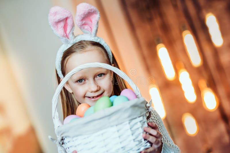 我爱庆祝复活节!逗人喜爱的女孩藏品篮子用复活节彩蛋和微笑 庆祝概念查出的白色 免版税库存照片