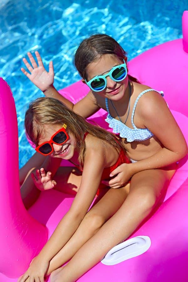 戴太阳镜,可膨胀的火鸟游泳浮游物的愉快的朋友的两个女孩画象  图库摄影