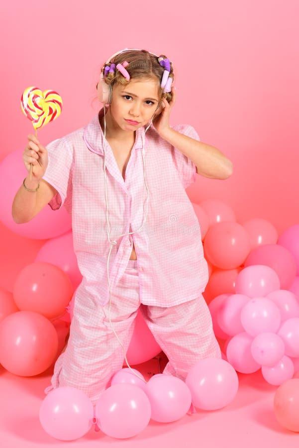 8或9岁吃大多色螺旋棒棒糖的儿童女孩 库存图片