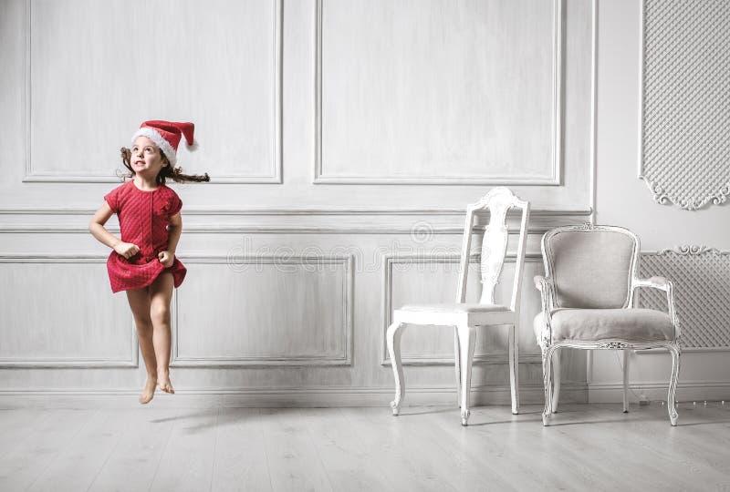 戴圣诞老人帽子的一个跳跃的女孩的画象 免版税库存照片