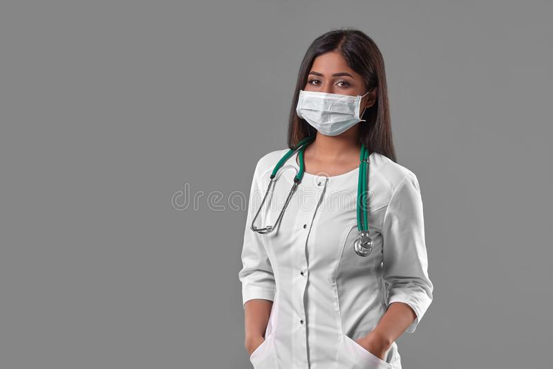 戴着与听诊器的年轻女性医生防毒面具 库存照片