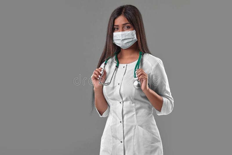 戴着与听诊器的年轻女性医生防毒面具 免版税库存照片