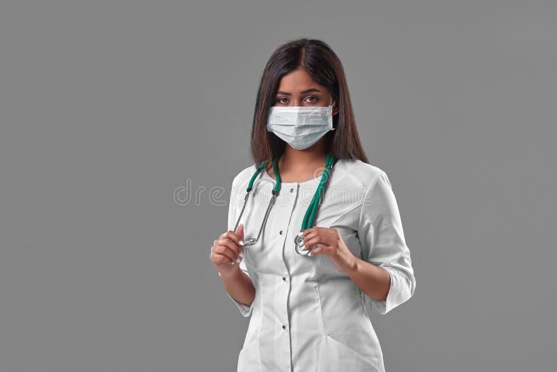 戴着与听诊器的年轻女性医生防毒面具 免版税图库摄影