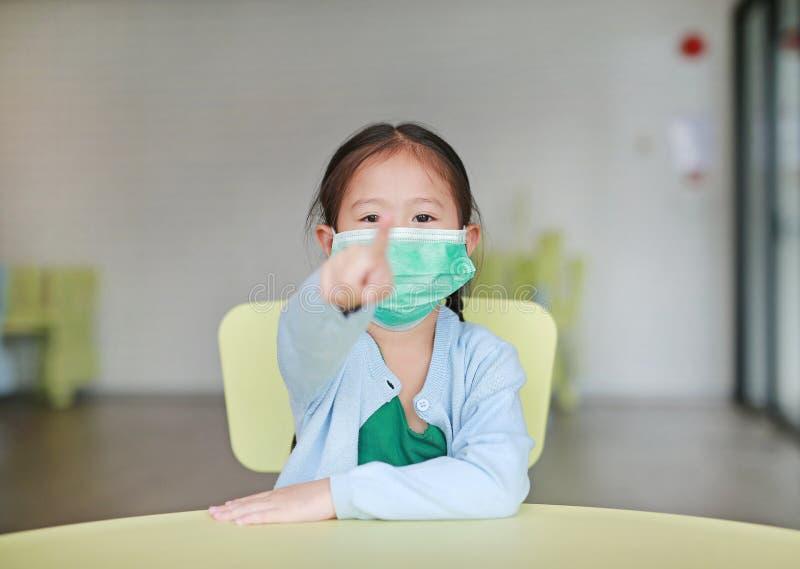 戴着与指向的逗人喜爱的矮小的亚裔儿童女孩一个防毒面具您坐孩子椅子在儿童居室 免版税库存照片