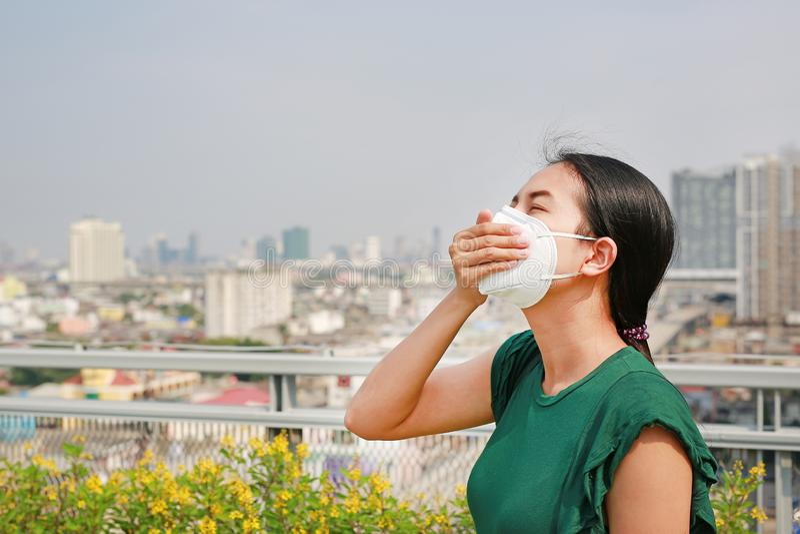戴着保护面具的年轻亚裔妇女反对PM 2 5空气污染在曼谷市 泰国 减少空气污染概念 免版税库存图片