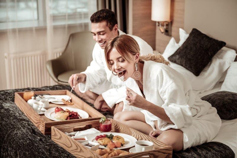 戴着时髦的耳环的金发的妻子吃早餐 库存图片
