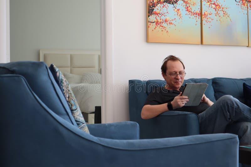 戴眼镜的一个人在片剂工作 放松在屋子里的人坐长沙发 感兴趣的可爱的人坐沙发 免版税库存图片