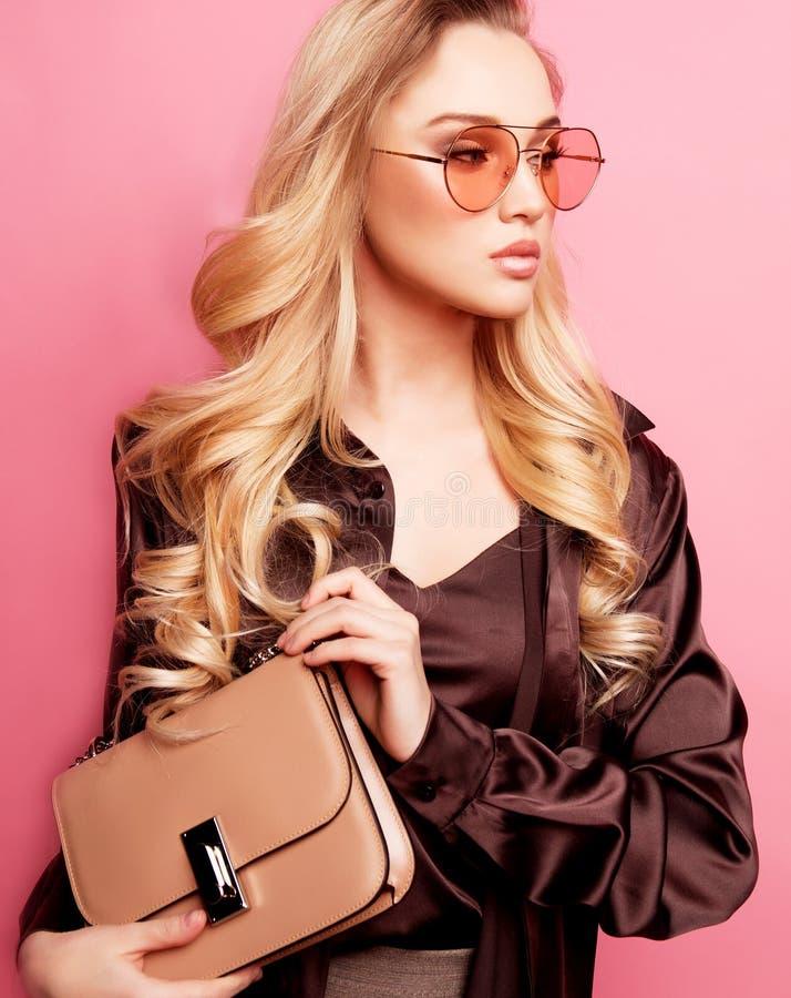 戴眼镜的女衬衫和裤子的美丽的白肤金发的妇女,拿着提包 免版税库存照片