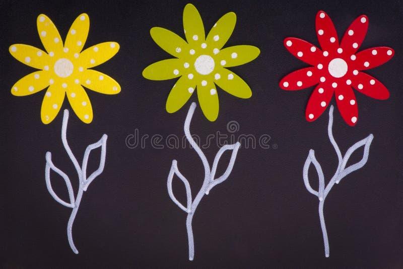 春天-在黑板的三朵花-木头材料 免版税图库摄影