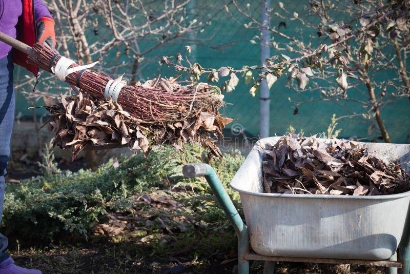 春季大扫除庭院的年长妇女 免版税库存照片
