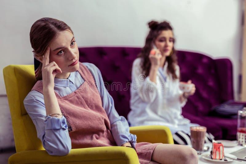 是桃红色的礼服的怀疑不快乐的女孩不满意的与她的朋友 库存照片