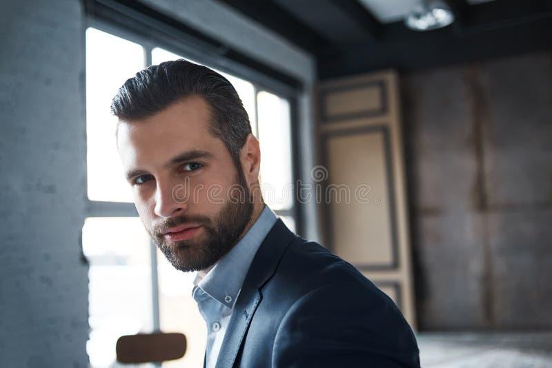 是成功的 看照相机,当站立在办公室时性感的有胡子的年轻商人的特写镜头画象  图库摄影